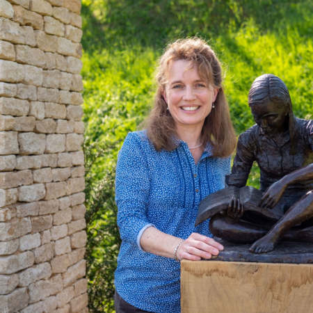 Anna Bromiley with her sculpture, Faith, installed in the garden.